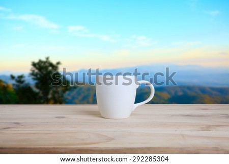 Cup of coffee on a wooden table and nature background.