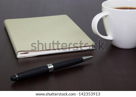 Cup of coffee on a wooden table with book and pen