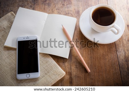 Cup of coffee on a wooden table with glass of water on the Sackcloth bags and smartphone and notebook and pencil. Simple workspace or coffee break with web surfing - stock photo