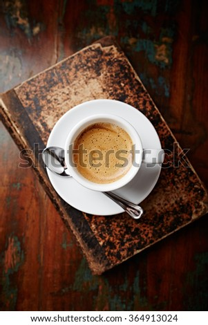 Cup of coffee on an old book - stock photo