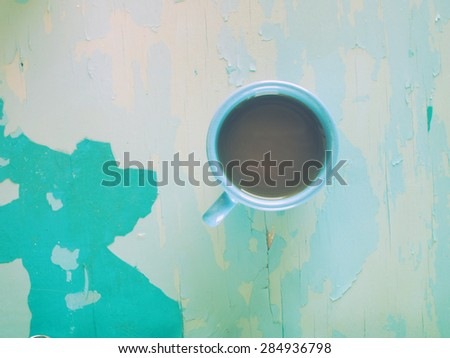 Cup of coffee on blue painted weathering table. Grunge style - stock photo