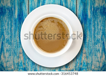 Cup of coffee on blue wooden surface, top view - stock photo
