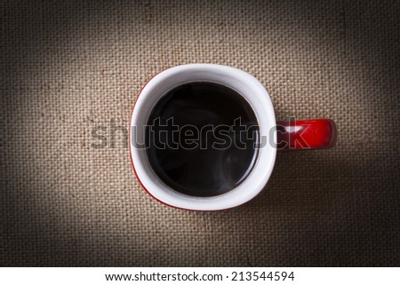 Cup of coffee on burlap, top view - stock photo