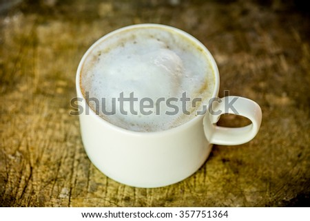Cup of coffee on grunge wooden table background