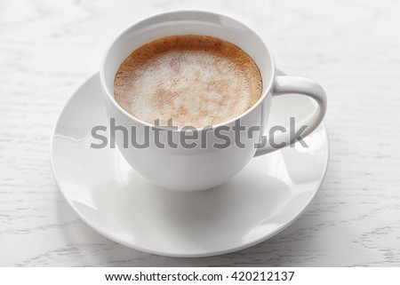 Cup of coffee on light wooden background