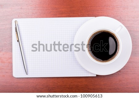 Cup of coffee on notepad top view