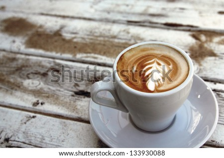 cup of coffee on old wooden table on the beach - stock photo