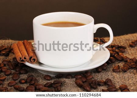 Cup of coffee on sacking on brown background