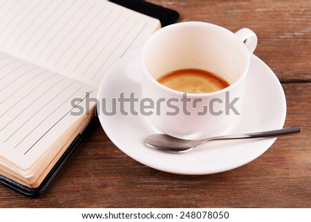 Cup of coffee on saucer with diary and spoon on wooden table background - stock photo