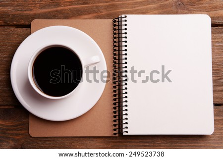 Cup of coffee on saucer with notebook on wooden table background - stock photo