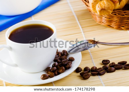 Cup of coffee on saucer with tea spoon and grain