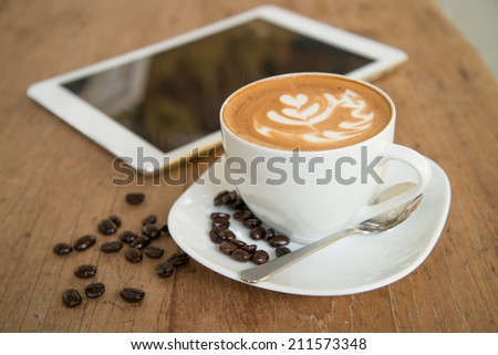 cup of coffee on table in cafe with tablet - stock photo