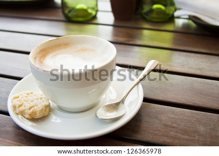 Cup of coffee on table in sun concept out of office taking a break - stock photo