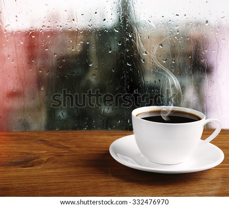 Cup of coffee on table on window background - stock photo