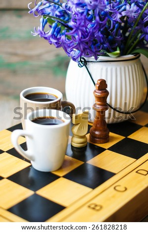 Cup Of Coffee On The Chess Board And First Spring Flowers