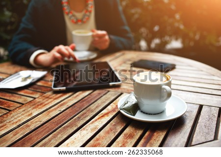 Cup of coffee on the foreground with elegant woman using busy touch screen tablet at the coffee shop wooden table, bill check and mobile phone near, flare sun light - stock photo
