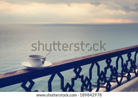 cup of coffee on the railing, with view on  sea at dusk - stock photo