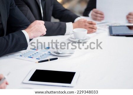 Cup of coffee on the table in business. Four confident successful businessmen at a meeting while sitting at a table discussing business doing in the office