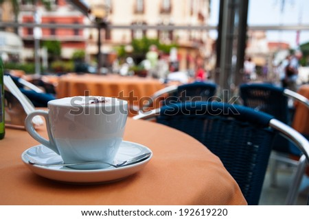 cup of coffee on the table of the outdoor cafe on the italian sidewalk. Taken during Italian vacation. - stock photo
