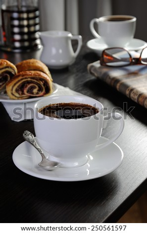 cup of coffee on the table with bread rolls and newspapers
