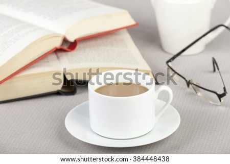 Cup of coffee on the table with two open books and a pair of eyeglasses - stock photo