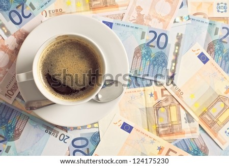 Cup of coffee on top of cash earnings from your business - stock photo