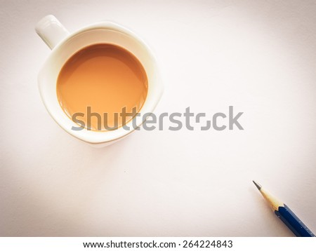 Cup of coffee on white table with pencil, Warm filter and vignette process