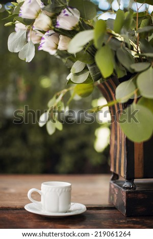 Cup of coffee on wooden table in summer cafe - stock photo