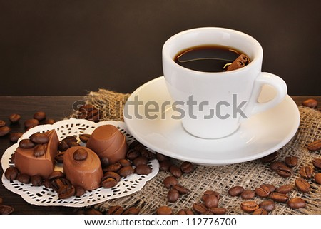 Cup of coffee on wooden table on brown background - stock photo