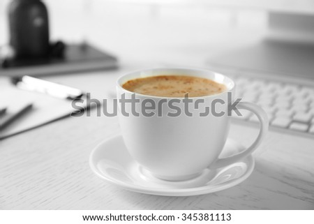 Cup of coffee on workplace background