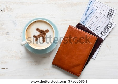 Cup of coffee, passports and no name boarding passes. Airplane made of cinnamon in coffee. Traveling concept. Cappuccino in airport  - stock photo