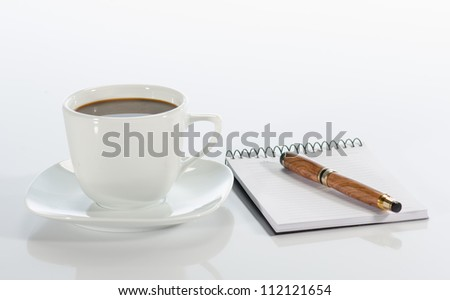 Cup of coffee, pen and notebook on white background - stock photo