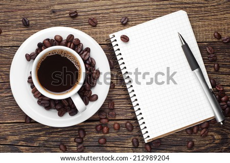 Cup of coffee, pen and opened notepad on desk. Top view - stock photo