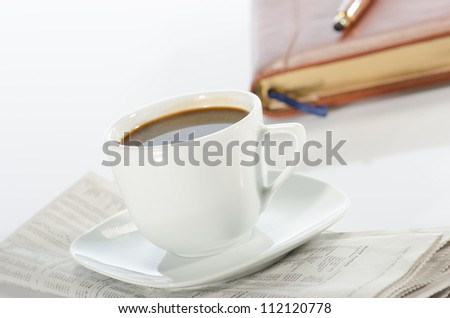 Cup of coffee, pen, notebook and newspaper against a  white background - stock photo