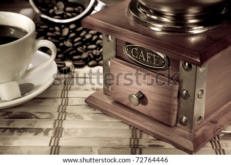 cup of coffee, pot with beans and grinder on vintage - stock photo