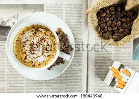 Cup of coffee, roasted beans and pack of cigarettes arranged on a newspaper - stock photo