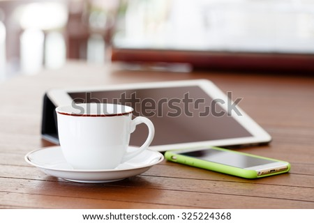 Cup of coffee, smartphone and tablet on wooden table