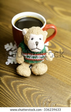 Cup of coffee, snowflake and toy monkey on wooden background.