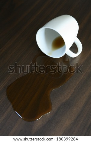 Cup of coffee spilled on wood table surface - stock photo