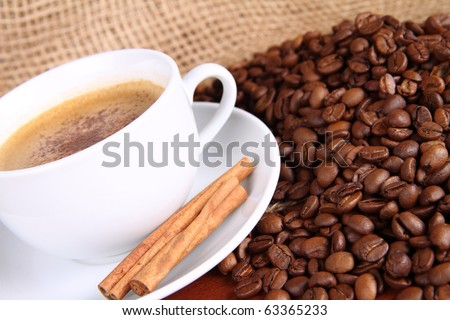 Cup of coffee sprinkled with cinnamon and with cinnamon sticks, coffee beans and burlap material