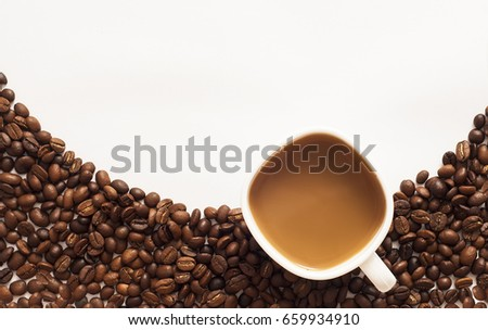 Cup of coffee surrounded by coffee beans on white background