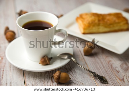 Cup of coffee, sweet buns and brown acorns