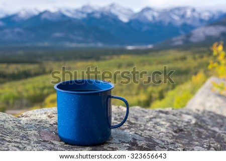 Cup of coffee/tea resting on cliff edge with beautiful view of mountains in background during Autumn.