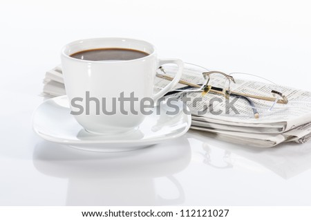 Cup  of coffee, the newspaper and the glasses isolated on white