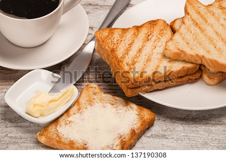 cup of coffee toast with butter on wooden table - stock photo