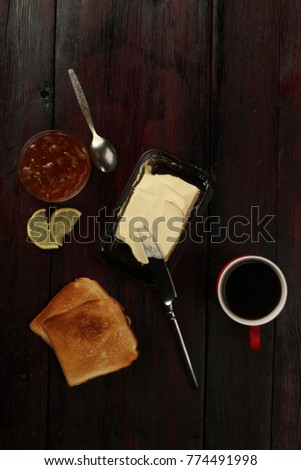 cup of coffee toast with butter on wooden table