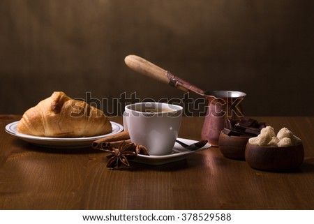 Cup of coffee, turkish pot, croissant, spices, brown sugar and chocolate on a dark background. - stock photo