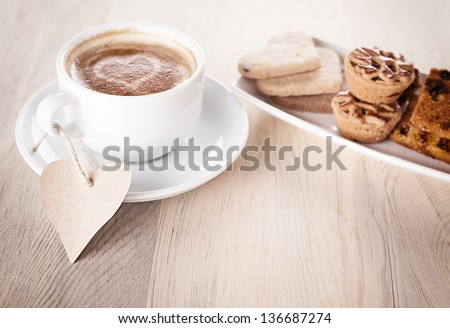 cup of coffee with a blank heart shaped note and cookies on wooden table - stock photo