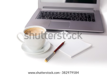cup of coffee with a laptop and a notebookv