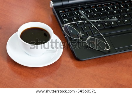 cup of coffee with a laptop and glasses close up - stock photo